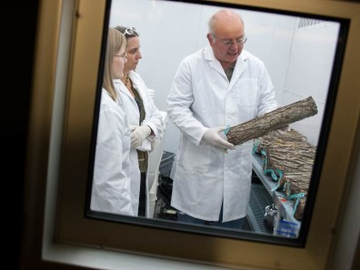 Man discusses log with associates in specimen isolation chamber.