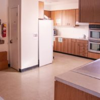 Large kitchen space with refrigerator, microwave, stove, and double wall ovens.