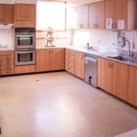 Large kitchen space with double wall ovens, dish washer and counter space.