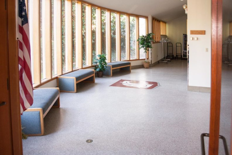 Building lobby with three benches and panoramic window onto garden area.
