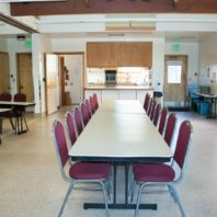 Two eight foot tables arranged end to end for meetings. Kitchen in the background.