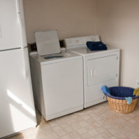 Lundry room with refrigerator, washin machine and clothes dryer.