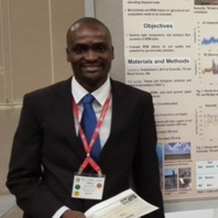 Man in suit stands next to a research poster.