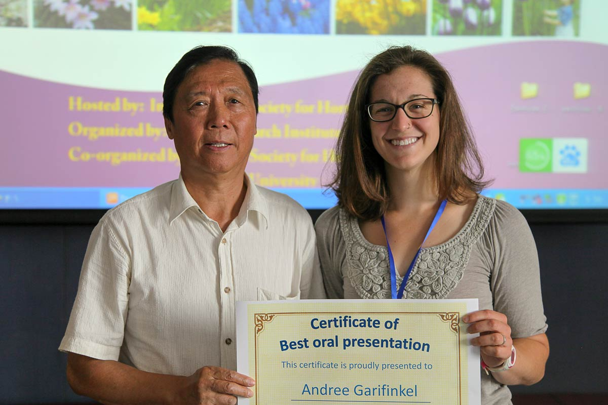 Chinese man presents certificate to female American graduate student.