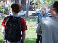 Dr. Chalker Scott talks to two students (backs to camera).