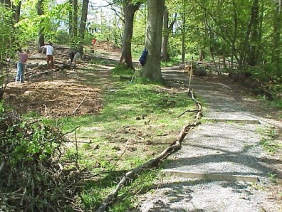 Using woody debris to edge a gravel path and keep mulch off the path.