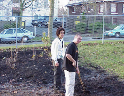 Two students pause with shovel while digging.