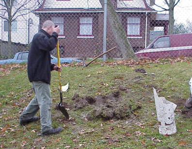 Digging planting holes with assistance from NOVA students.
