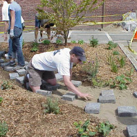 Installing pavers to create a path through the big bed.