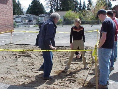 Examining the soil following asphalt removal.