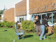 Removing weeds and turf from the planting bed near the school.