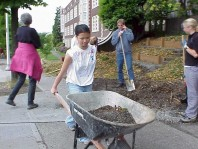 Garfield students move soil and mulch near the newly installed terrace.