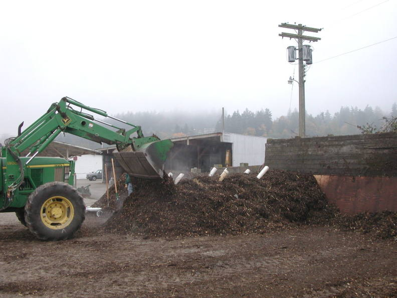 Photo of tractor mixing compost.