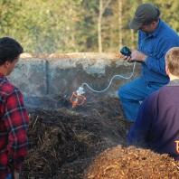Three men, compost pile