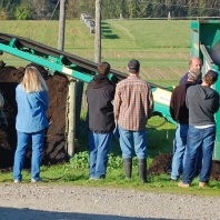 Small group of people, tractor and trommel separator