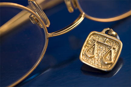 Old fashioned spectacles lying next to small gold scale charm