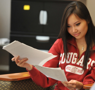 woman in red cougar shirt examining papers