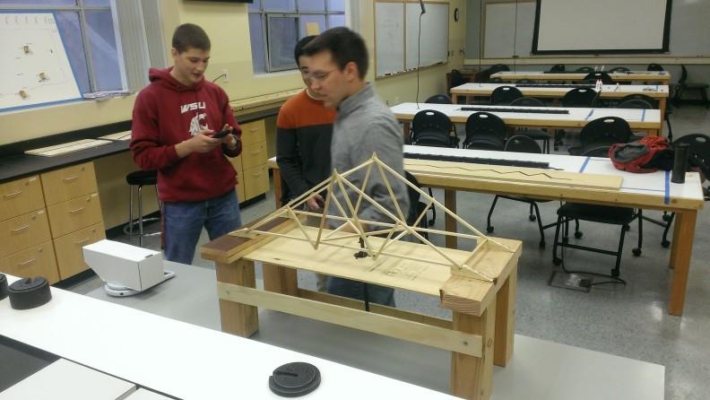 Three students working on a model bridge.