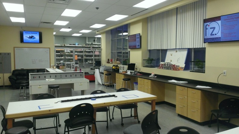 Maker space with tables, whiteboard, and monitors.
