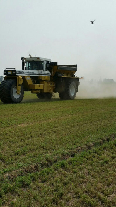 Drone flies over spreader applying struvite to a field.
