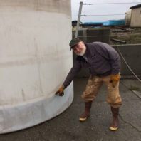 Joe Harrison points to liquid level on the outside of a large plastic tank.