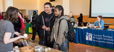 Coug Health Fair Image from 2015, vendor talking to student