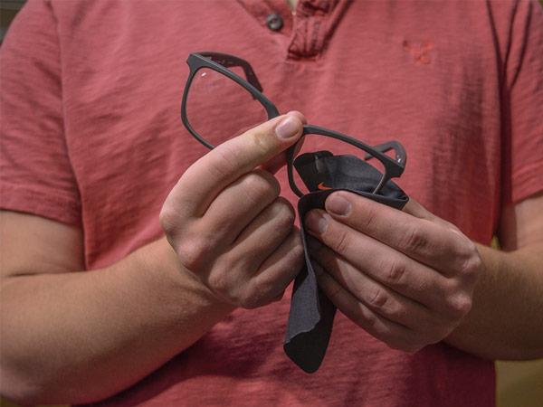 Student cleaning eyeglass lenses