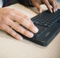 Close up of hands on a computer keyboard