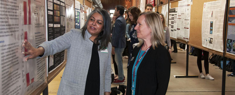 researcher explaining her work to faculty member at the 2018 Inland Northwest Research Symposium on campus