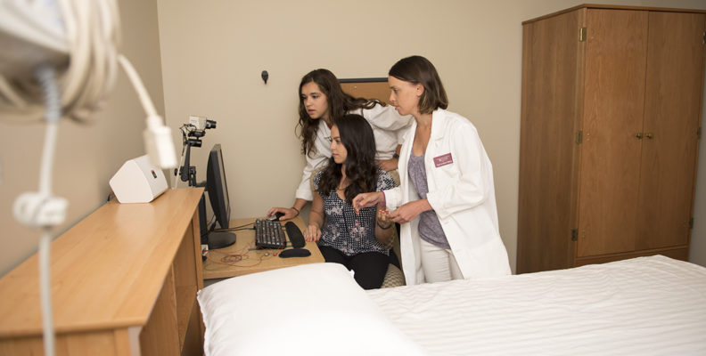 Research assistants Samantha Riedy, Regan Permito, and Beth Lewis (front to back) review a cognitive performance test while preparing for a sleep deprivation study in the laboratory at WSU Spokane.