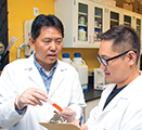 Researcher Zhenjia Wang talks to a graduate student in his lab