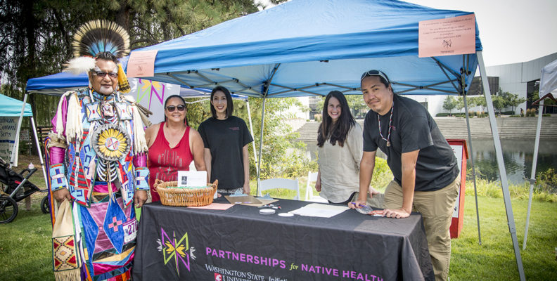 Ka'imi Sinclair and team members from the Partnerships for Native Health talk to a Native American dancer while doing outreach at a powwow in Spokane.