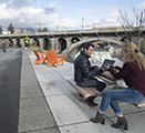 Image showing researcher Ofer Amram working on a laptop at a bench next to the Centennial Trail in Spokane, as pedestrians walk by.