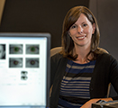 Researcher Georgina Lynch sits behind a screen that shows pupil dilation data and images.