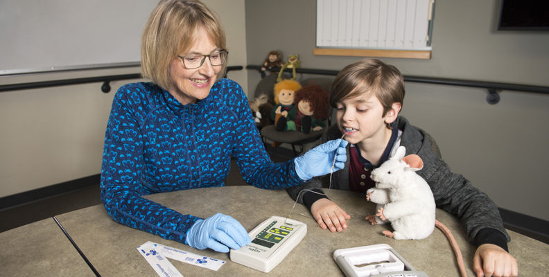 Nancy Potter uses a device that measures tongue strength on a young boy.