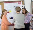 DNP graduate Jaclyn Thatcher, right, talks about her project on group medical visits for patients with chronic pain at the Inland Northwest Research Symposium in late April.
