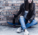 Young woman dressed in hoodie is sitting on skateboard and holding smoldering cigarette and bottle of beer.