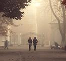People walking through a park under smoky skies