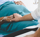 Nurse holding hand of pregnant patient in hospital bed