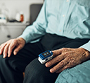 A senior man is shown with a pulse oximeter on his index finger.