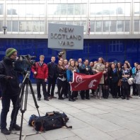 WSU and UI students, Dr. Neuilly, Sisouvanh Keopanapay, and Dr. Wolf (along with UI mascot Joe Vandal) pose outside of New Scotland Yard while news camera crews set up for an upcoming news conference. March 16, 2015.