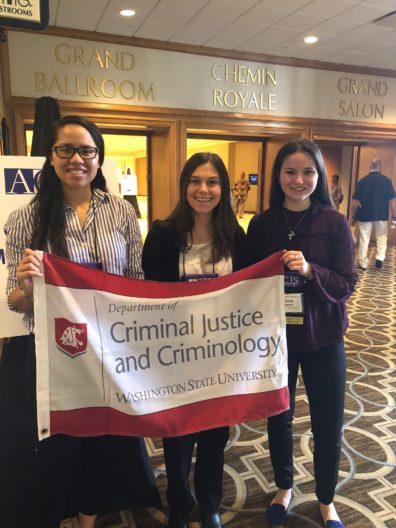 3 undergraduates hold the Criminal Justice & Criminology banner.