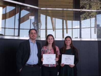 Dr. Dale Willits stands with students Emma Smith & Samantha Bill, who are holding award certificates..
