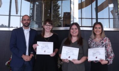 Dr. David Makin stands with students Staci Friede, Emily Martin, & Isobel Luengas, who are displaying their award certificates..
