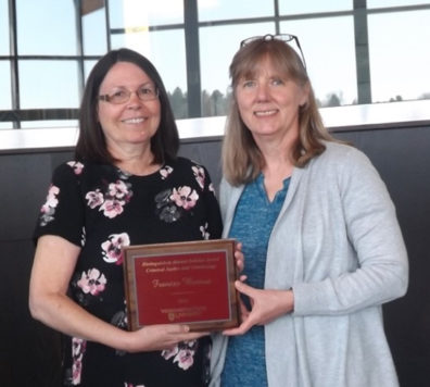Alumna Frances Bernat receives her award placque from Professor Faith Lutze.
