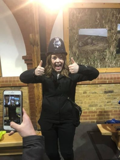 Graduating Criminal Justice and Criminology major Emily Bartlett giving the thumbs up while wearing a Bobby's uniform during a visit with the Metropolitan Police Youth Cadets Program.