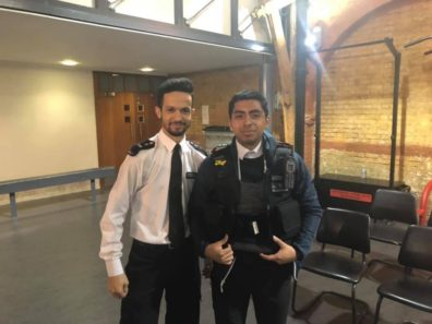 Junior Criminal Justice and Criminology major Manuel Ortiz-Rodriguez poses in a Metropolitan Police vest with an officer volunteer during a visit to the Metropolitan Police Youth Cadets Program.