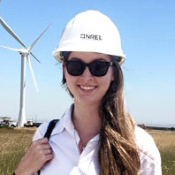 Photo of Alyssa Norris in hard hat posing near a wind mill
