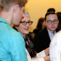 Nancy Swanger speaking with students at her table.