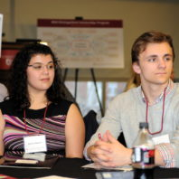 Two students look toward the right and listen as a table speaker talks out of frame at the Freshman Scholars Progression 2018 event